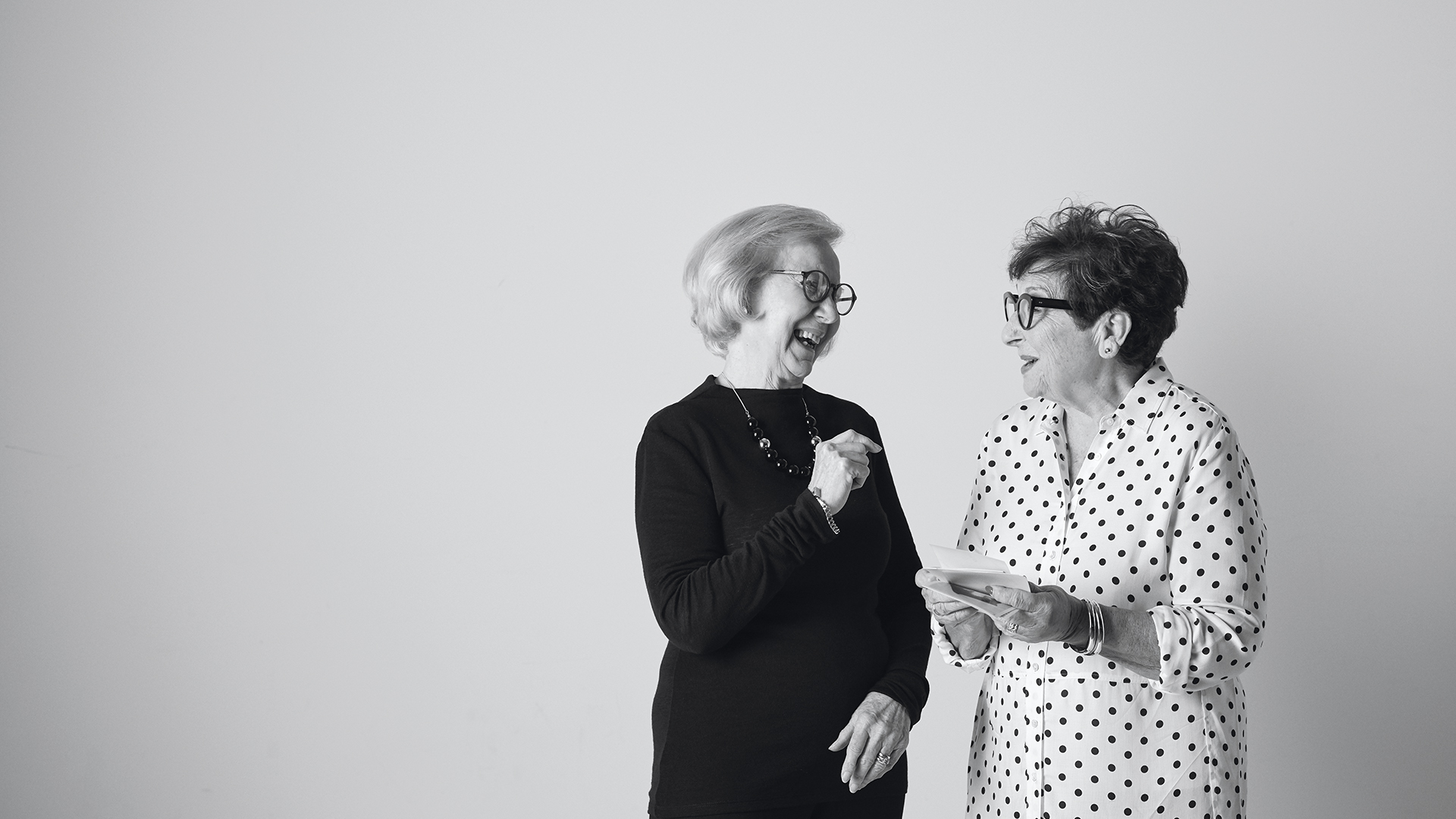 Black and white image of two stylish senior ladies talking an laughing at Morgan Glen Iris